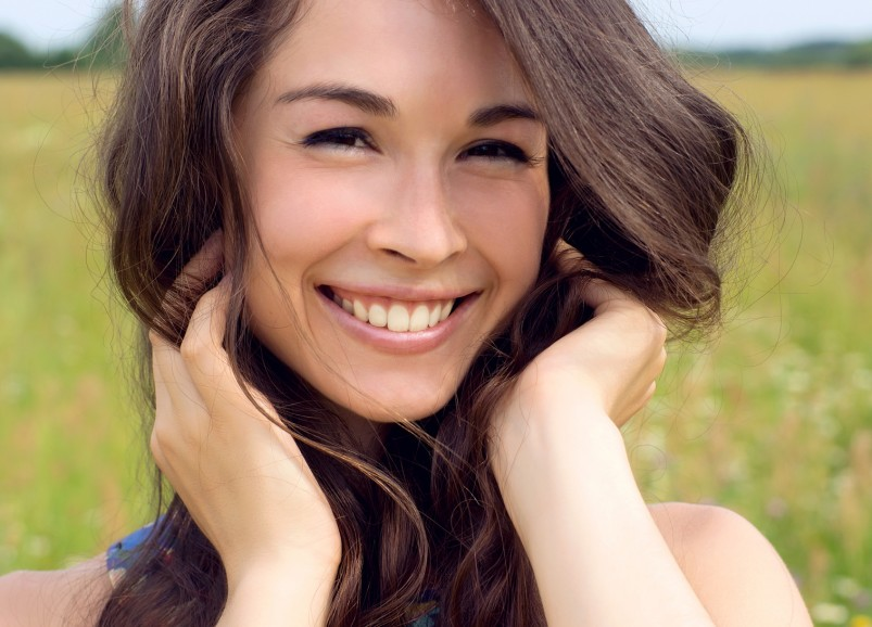 Happy young beautiful woman in field